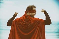 Man in superhero costume standing at sea shore Stock Photos