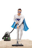 Man in a superhero costume vacuuming a carpet Stock Photography