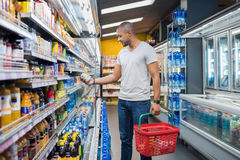 Man at supermarket. African man shopping in beverage section at supermarket. Black man doing shopping at market while buying cold drink. Handsome guy holding Royalty Free Stock Image