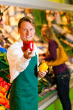 Man in supermarket as shop assistant Stock Images