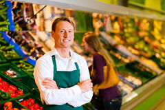 Man in supermarket as shop assistant Royalty Free Stock Images