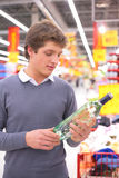 Man in supermarket with bottle of alcohol Stock Photo