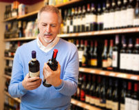 Man choosing wine. Man in a supermarket choosing the right wine Stock Image