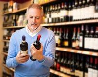 Man choosing wine. Man in a supermarket choosing the right wine stock image