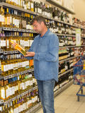 Man in a supermarket choosing a wine bottle stock photos