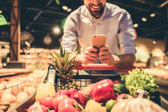 Man at the supermarket. Cropped image of handsome man using a mobile phone and smiling while doing shopping at the supermarket Royalty Free Stock Image