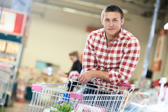 Man at supermarket dairy shopping. Man with shopping cart with food produces in supermarket Royalty Free Stock Photos