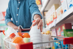 Man at the supermarket. Man doing grocery shopping at the supermarket, he is putting a bottle of milk in the cart Royalty Free Stock Photo