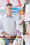 Man at the supermarket. Man doing grocery shopping at the supermarket, he is taking a box from the store shelf Royalty Free Stock Photography