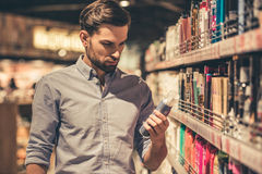 Man at the supermarket. Handsome man is choosing cosmetics while doing shopping at the supermarket Stock Photo