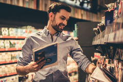 Man at the supermarket. Handsome man is choosing a magazine and smiling while doing shopping at the supermarket Royalty Free Stock Photos