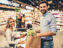 Man at the supermarket. Handsome men and beautiful female cashier are smiling while standing at the cash desk in the supermarket Royalty Free Stock Image