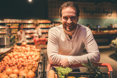 Man at the supermarket. Handsome men is looking at camera and smiling while doing shopping in supermarket Royalty Free Stock Image