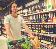 Man in the supermarket. Handsome young man is pushing a shopping cart and smiling while choosing beverages in the supermarket Stock Photos