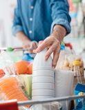 Man at the supermarket. Man doing grocery shopping at the supermarket, he is putting a bottle of milk in the cart Royalty Free Stock Image