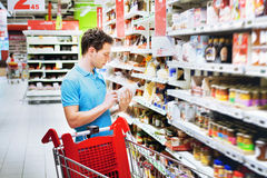 Man in supermarket. Man reading label on the bottle in supermarket Royalty Free Stock Images