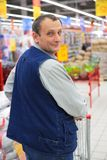 Man in supermarket with shopping cart. Man in modern supermarket with shopping cart Stock Photos
