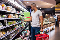 Man at supermarket. Young african man buying vegetables in grocery section at supermarket. Black man choose vegetables in the supermarket while holding grocery Royalty Free Stock Photo