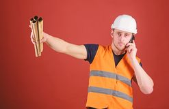 Man supervises construction on phone, red background. Engineer, architect on busy face speaks on phone, holds blueprints. Pointing with finger, copy space royalty free stock photography