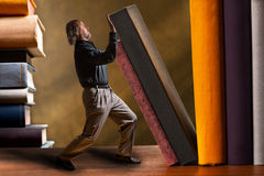 Man supporting falling book in the bookshelf Royalty Free Stock Images