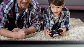 Man supporting his little son playing video game at home, family relationship. Stock photo stock photos