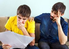 Two Sad Men. Man supporting upset Friend and touching his Shoulder on the Sofa. Bad news concept stock photography
