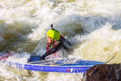 The man supsurfing on the rapids of the mountain river. The man fell from SUP surfing on the rapids of the mountain river stock image