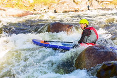 The man supsurfing on the rapids of the mountain river. The man fell from SUP surfing on the rapids of the mountain river stock images