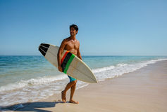 Man with surf board on beach. Full length shot of young man with surf board on beach. Handsome caucasian male holding surfboard walking on the sea shore and Royalty Free Stock Photo