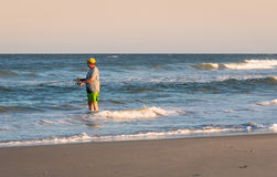 Man Surf Fishing. Older man wading into the ocean to fish Royalty Free Stock Image