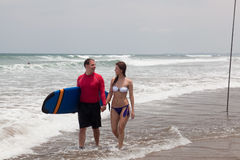 Man with surf and the girl. Go on an ocean coast Royalty Free Stock Image