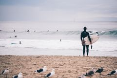 Man with surfboard looking at the waves Stock Image