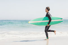 Man with surfboard running towards sea Stock Images