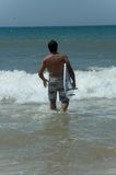 Man with surfboard in sea. Rear view of man walking into sea with surfboard Stock Images