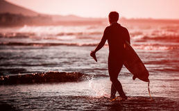 Man with a surfboard. Silhouette of man with a surfboard on the beach Stock Photos