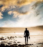 Man with a surfboard. Silhouette of man with a surfboard on the beach at sunset Royalty Free Stock Image
