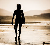 Man with surfboard. Silhouette of the man walking on the beach with the surfboard Stock Images