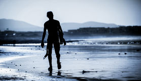 Man with surfboard. Silhouette of the man walking on the beach with the surfboard Stock Photo