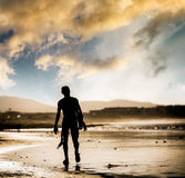 Man with surfboard. Silhouette of the man walking on the beach with the surfboard at sunset Stock Photos