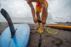 Man with a surfboard. Surfer getting on the surfboard`s leash Stock Images