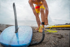 Man with a surfboard. Surfer getting on the surfboard`s leash Royalty Free Stock Photos