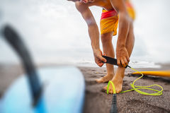 Man with a surfboard. Surfer getting on the surfboard`s leash Royalty Free Stock Photography