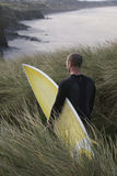 Man With Surfboard Walking Through Grass On Beach Stock Image