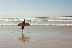 Man with surfboard walking on shore Stock Photo