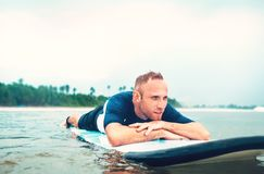 Man surfer rests lying on surfboard Royalty Free Stock Photo