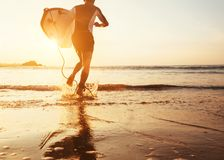 Man surfer run in ocean with surfboard in sunset light Royalty Free Stock Photography