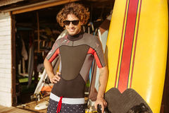 Man surfer in sunglasses standing on the beach. Happy young man surfer in sunglasses standing on the beach Stock Images