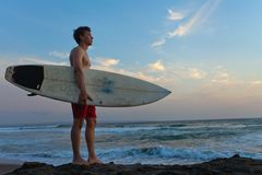 Man surfer with surfboard on a coastline Royalty Free Stock Image