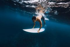 Man surfer with surfboard dive underwater of big ocean wave. royalty free stock images