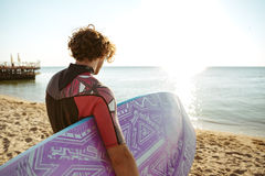 Man surfer with surfing board on the beach. Back view of curly young man surfer with surfing board on the beach Royalty Free Stock Photo